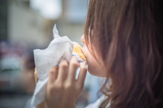 ドーナツを頬張る女性
