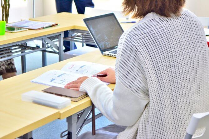資料とパソコンを広げる女性