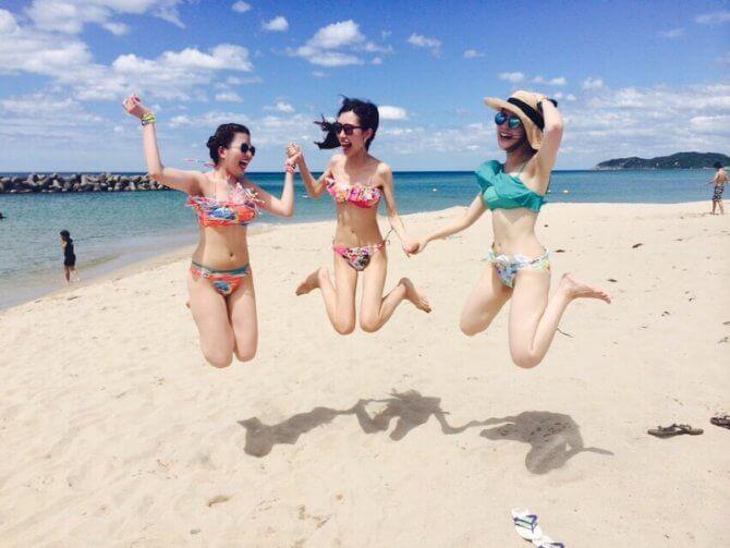 真夏のビーチでジャンプするイケてる女性3人組