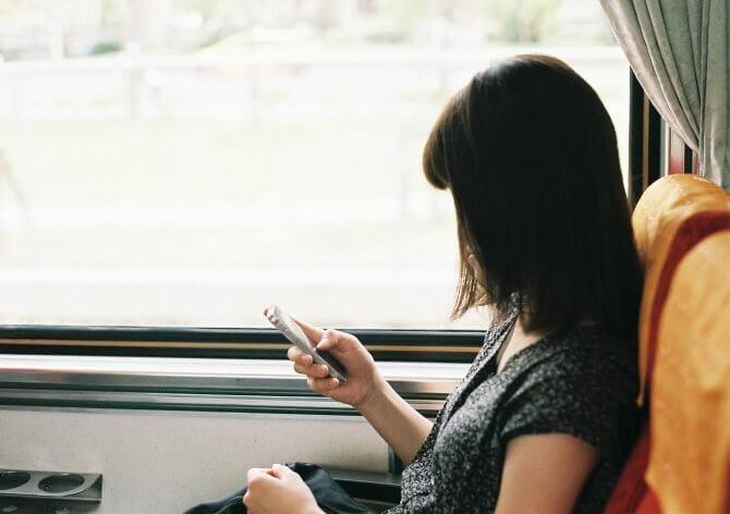 電車でスマホをする女性