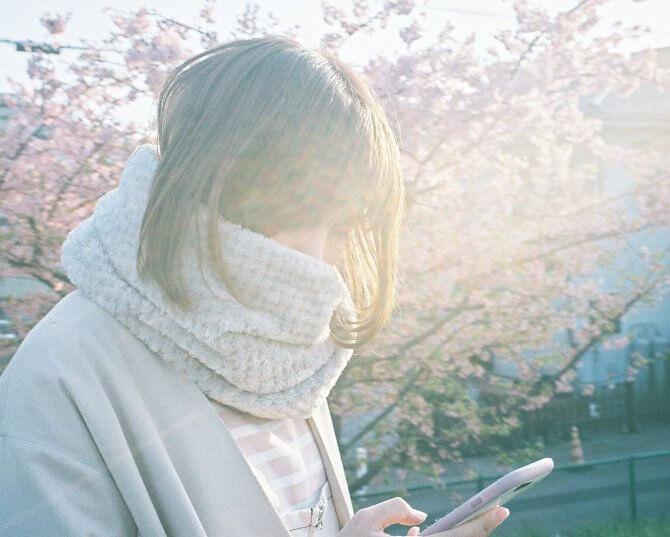 桜とスマホをいじる女性