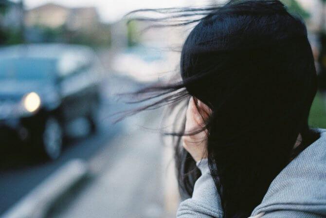 顔を覆う黒髪女性の横顔