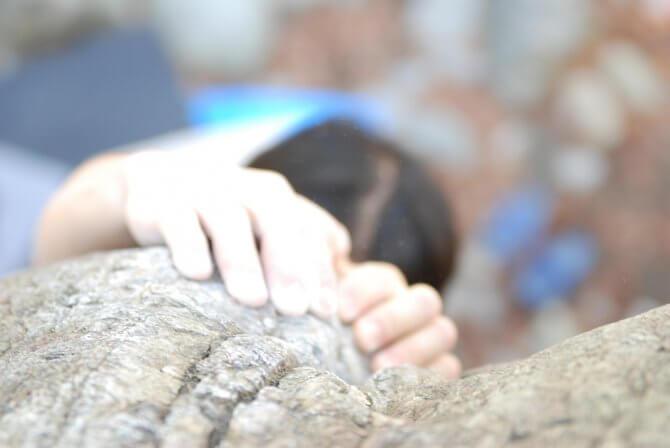 岩にしがみついて登ろうとしている人