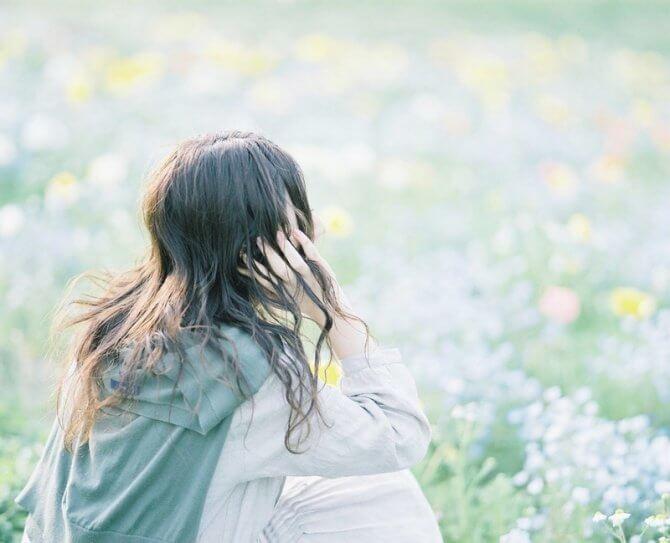 お花畑を眺める座っている女性