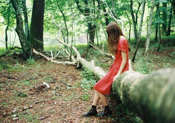 森の木に座る赤いワンピースの女性