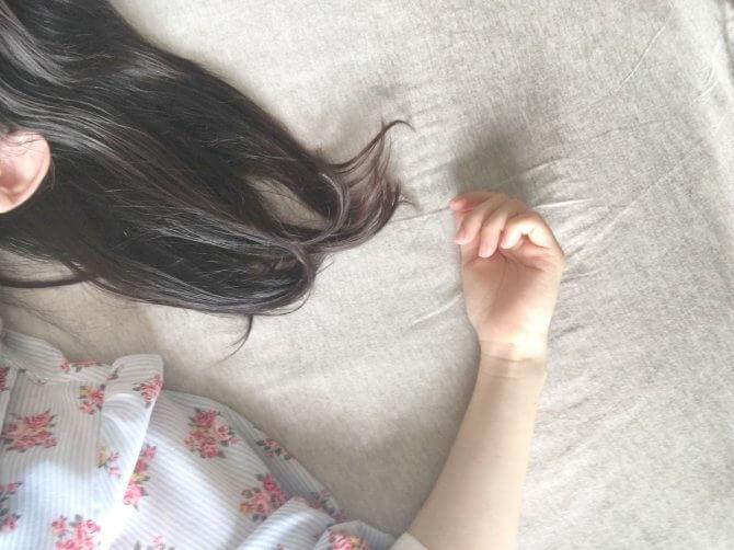 ベッドで仰向けの女性の手