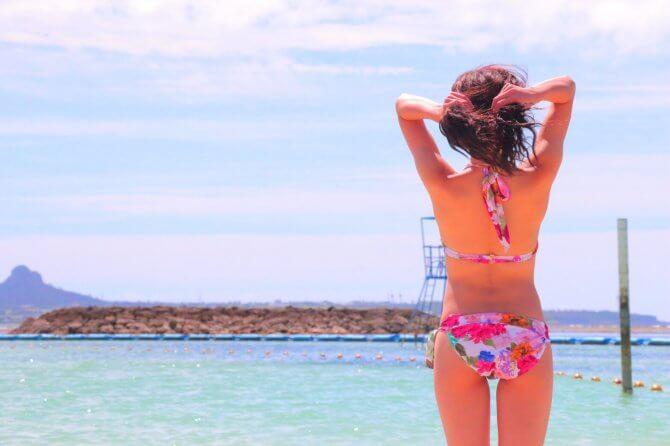 海を眺めるボディラインがきれいな女性