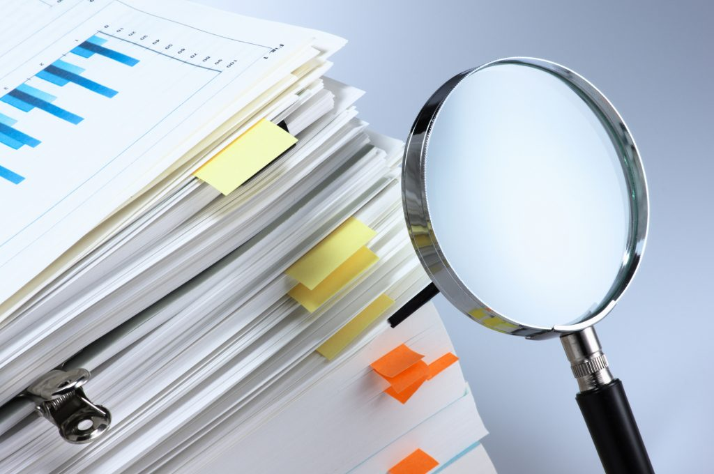 Magnifying glass and stack of documents.