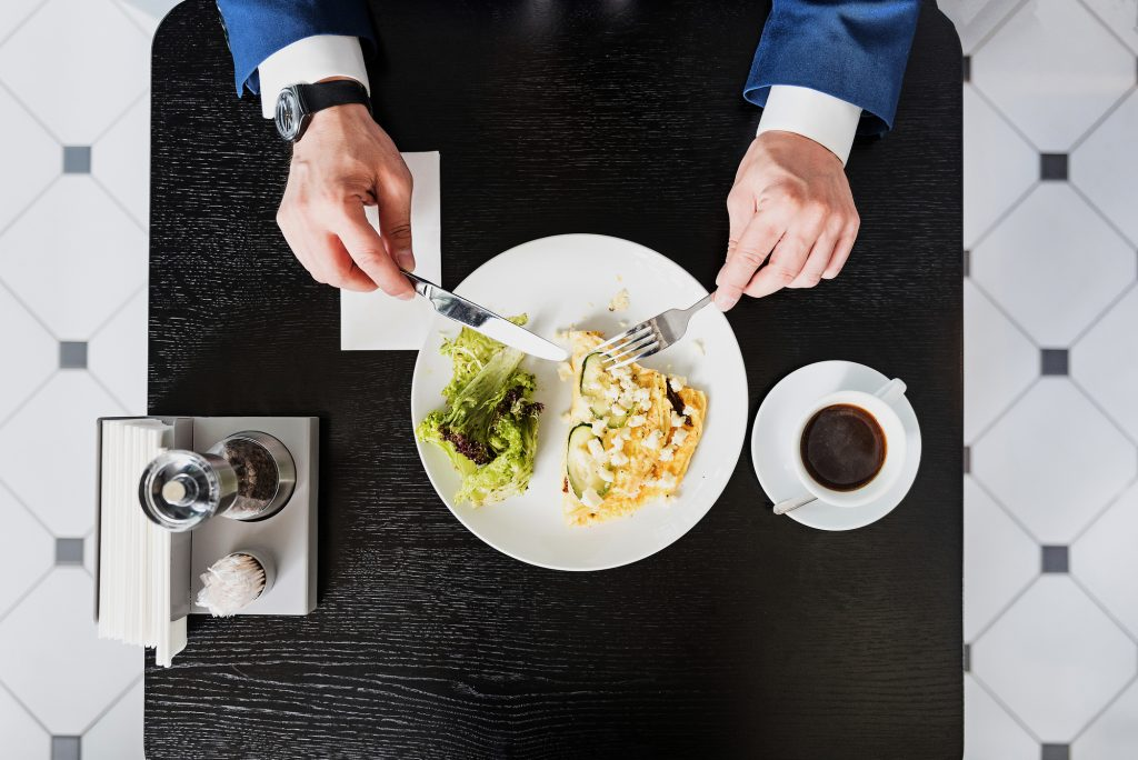 Top view of male hands dining in restaurant. Man in suit is holding fork and knife under the plate. Cup of coffee is on table. Close up