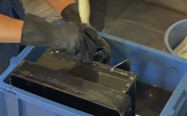 プロの換気扇クリーニングの業者さんが分解してつけおきしたフードを特徴的なブラシで洗う様子