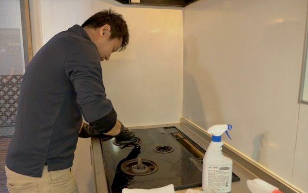 ガスコンロの天板を掃除するプロのキッチンクリーニングの業者さん