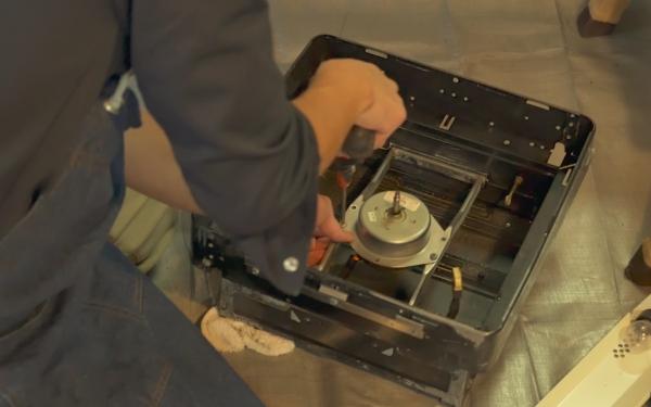 プロの換気扇クリーニングの業者さんが分解洗浄をしたあとの換気扇を組み立てる様子