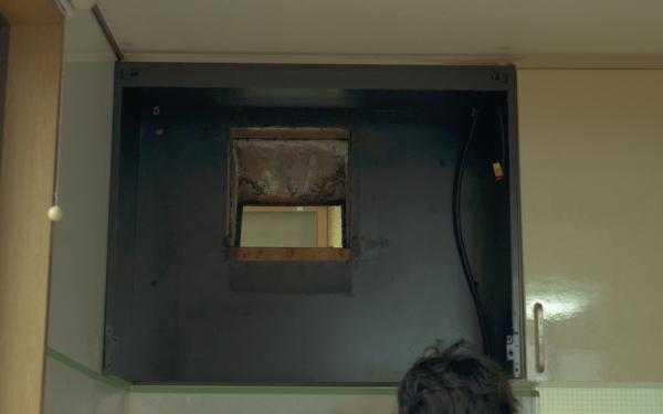 分解された換気扇から外を覗く穴