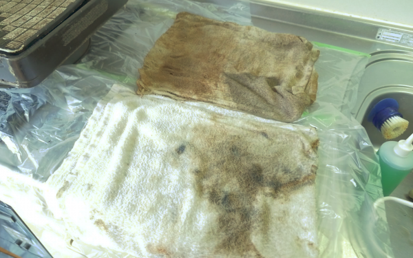 プロの換気扇クリーニングの業者さんが換気扇を掃除して茶色く汚れた白いタオル