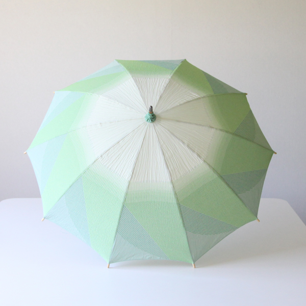 葉野菜の何枚も葉が重なる様子が表現されたグリーンと薄いクリーム色が爽やかな日傘