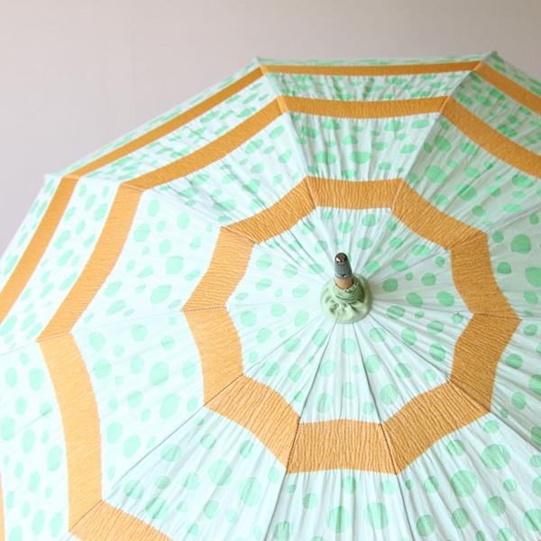 円を描くように広がるオレンジ色のラインと、緑色の豆模様が外側に弾けているような