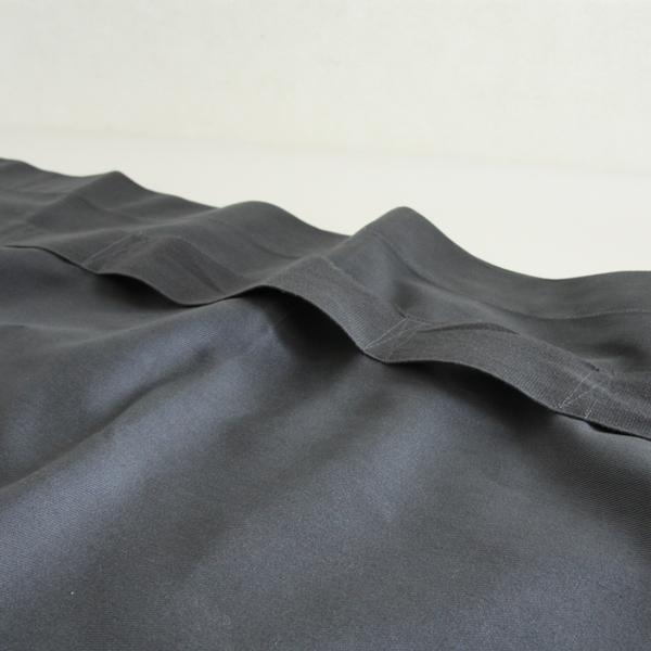腰の部分に縫い付けられた布テープの隙間にエプロンの端を入れ込むようにして身に付けます