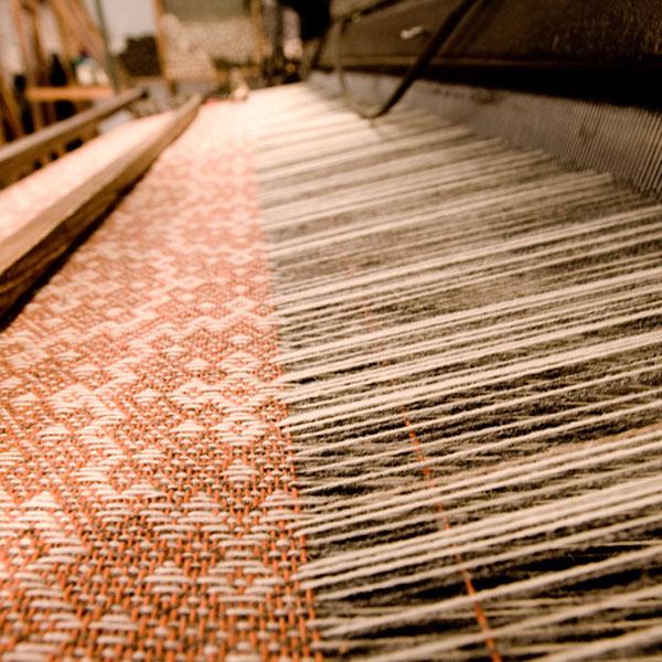 ウール生地が織り上げられる様子