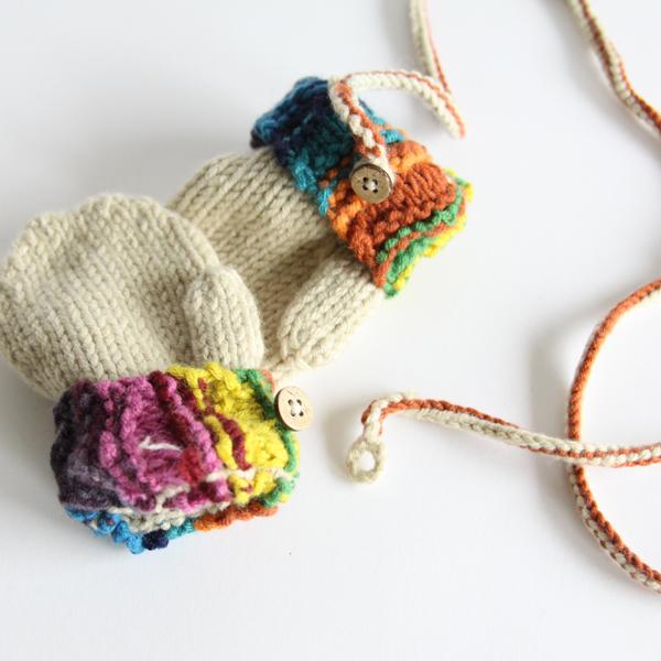 優しいオフホワイトに、カラフルな毛糸のデザインがかわいい手袋です