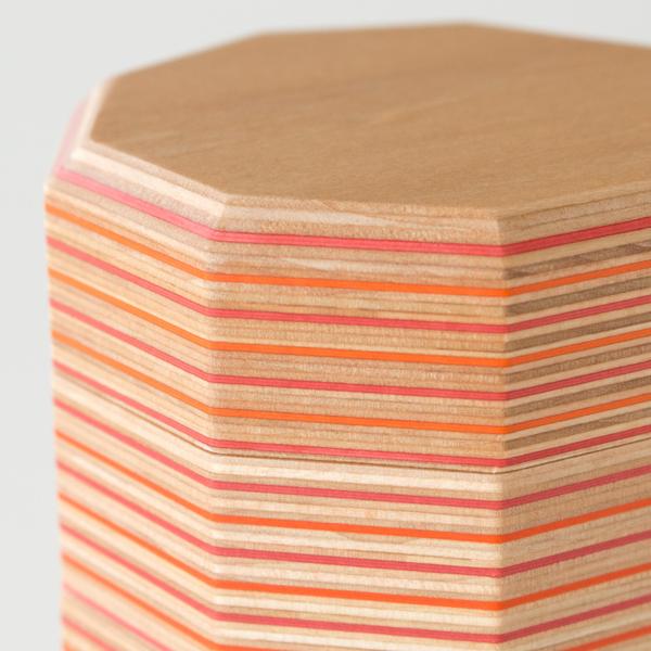 積層された板の間に鮮やかな色の再生紙を挟むことで出来上がる「Paper-wood」