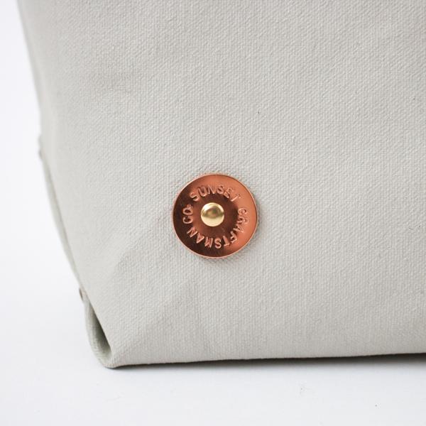 手作業で丸く切り出した銅のプレートに、一文字ごとに刻印を施します(BROWN/NIMBUS)