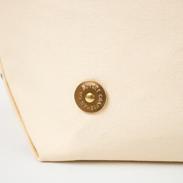 手作業で丸く切り出した銅のプレートに、一文字ごとに刻印を施します