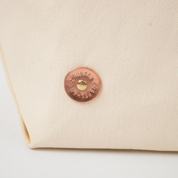 手作業で丸く切り出した銅のプレートに、一文字ごとに刻印を施します(BROWN/MILK)
