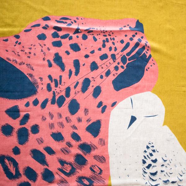 ヒョウとフクロウがぴたりと顔を寄せっています
